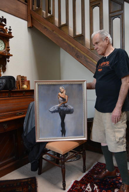 Robert W Moore Fine Art artist standing in the foyer of his beautiful home touching the frame of his signature piece, The Ballerina